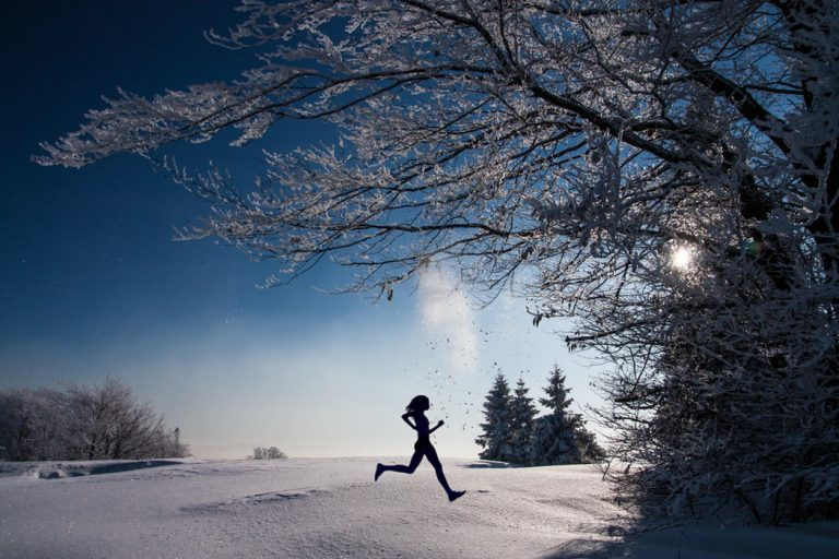 Silhouette of person running across snowy field