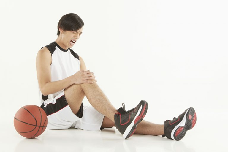 Injured basketball player sitting on the ground