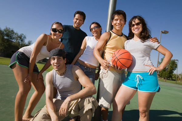 Friends posing for picture with basketball